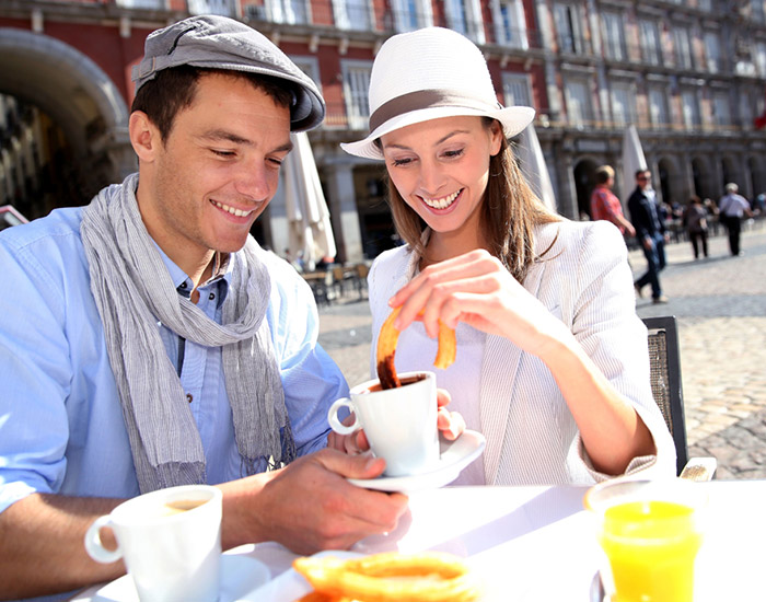 Couple eating churros and chocolate in Madrid